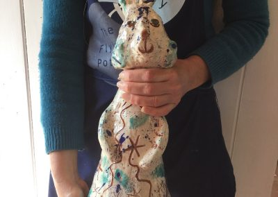 sarah monk holding her ceramic slipware rabbit in the doorway at eastnor pottery