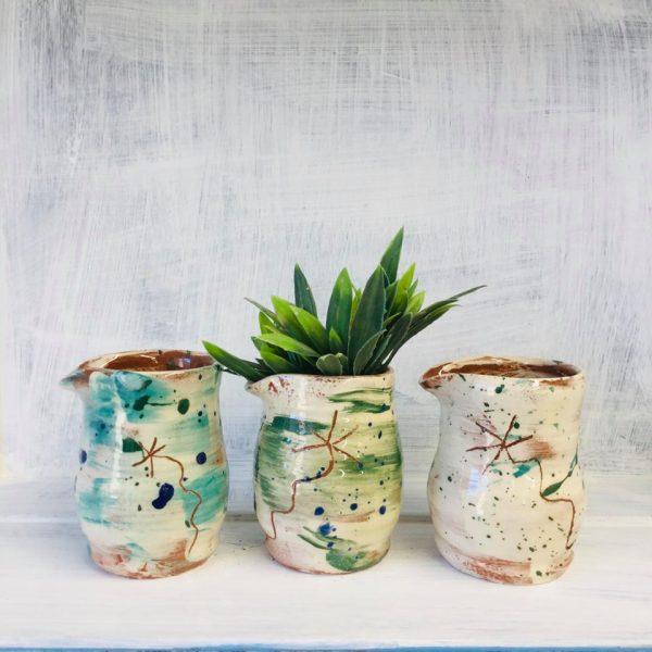 three slipware jugs in a row