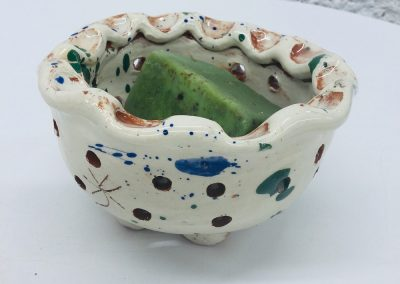 a handmade soap colander by sarah monk ceramics in white with a pie crust rim along with chunky soap