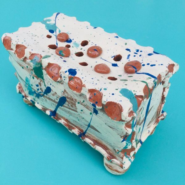 rectangular sopa pillow with paint splatters and blobs of clay on the top that look like chocolate buttons by sarah monk