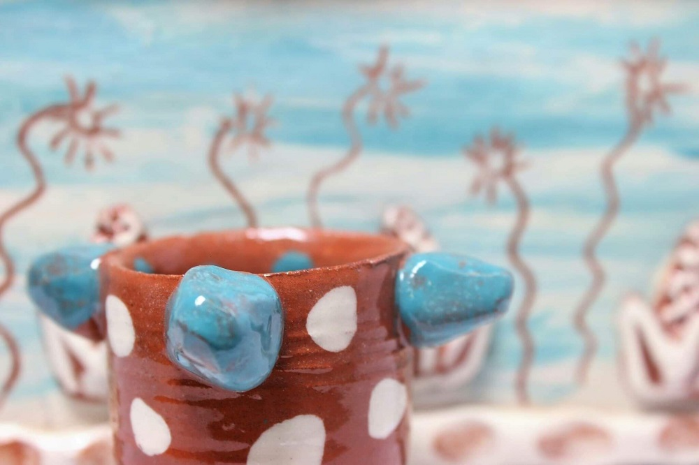close up detail of a hand thrown terracotta egg cup with white dots and blue blobs by sarah monk