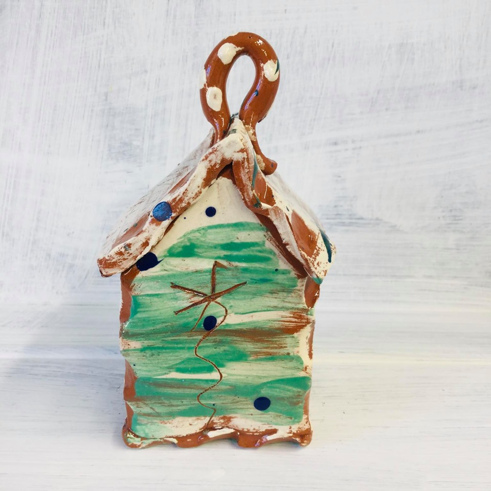 brushed sea green bug house on a white shelf