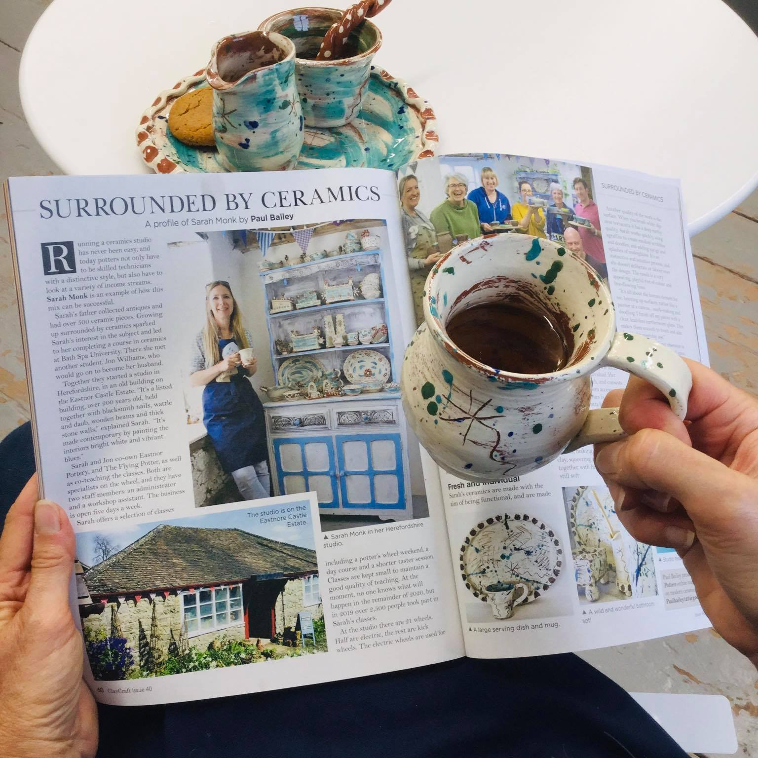 holding a slipware cup with tea inside and holding magazine article