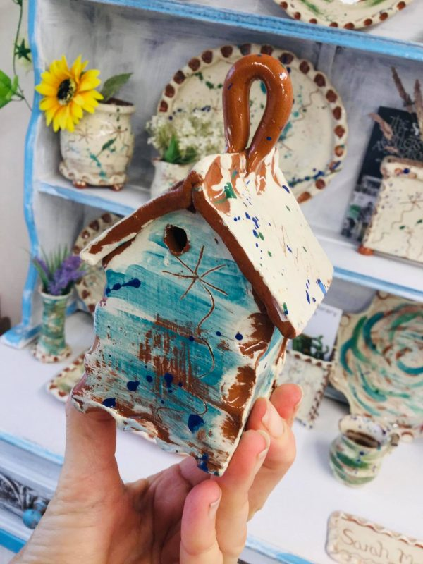 sarah monk hand shotholding teal bug house in eastnor pottery