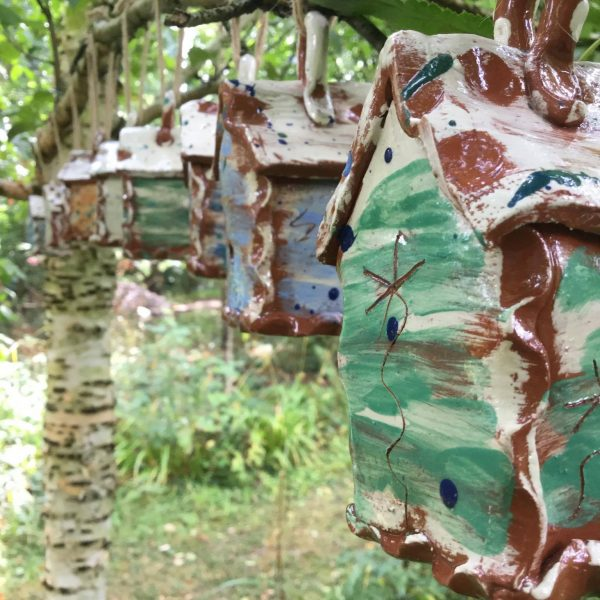 four bug houses hanging on a tree made by sarah monk ceramics
