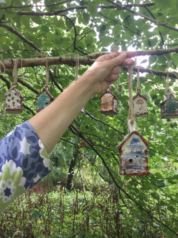 arm shot of sarah monk holding up a ceramic bughouse in a woodland