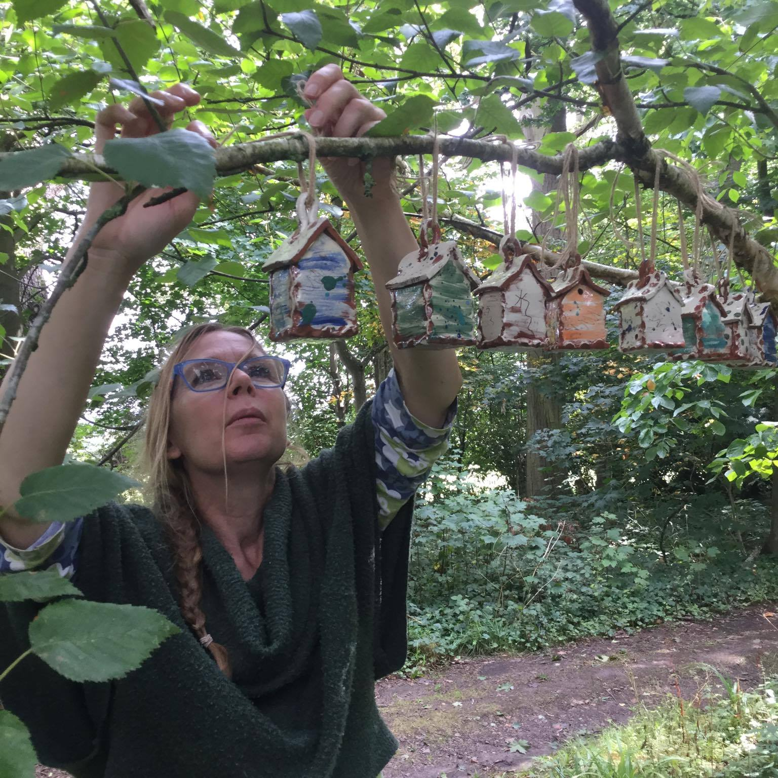 sarah monk hanging up her slipware bug houses in a tree at hellens manor