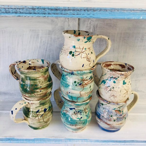 stack of slipware mugs on the shelf made by sarah monk