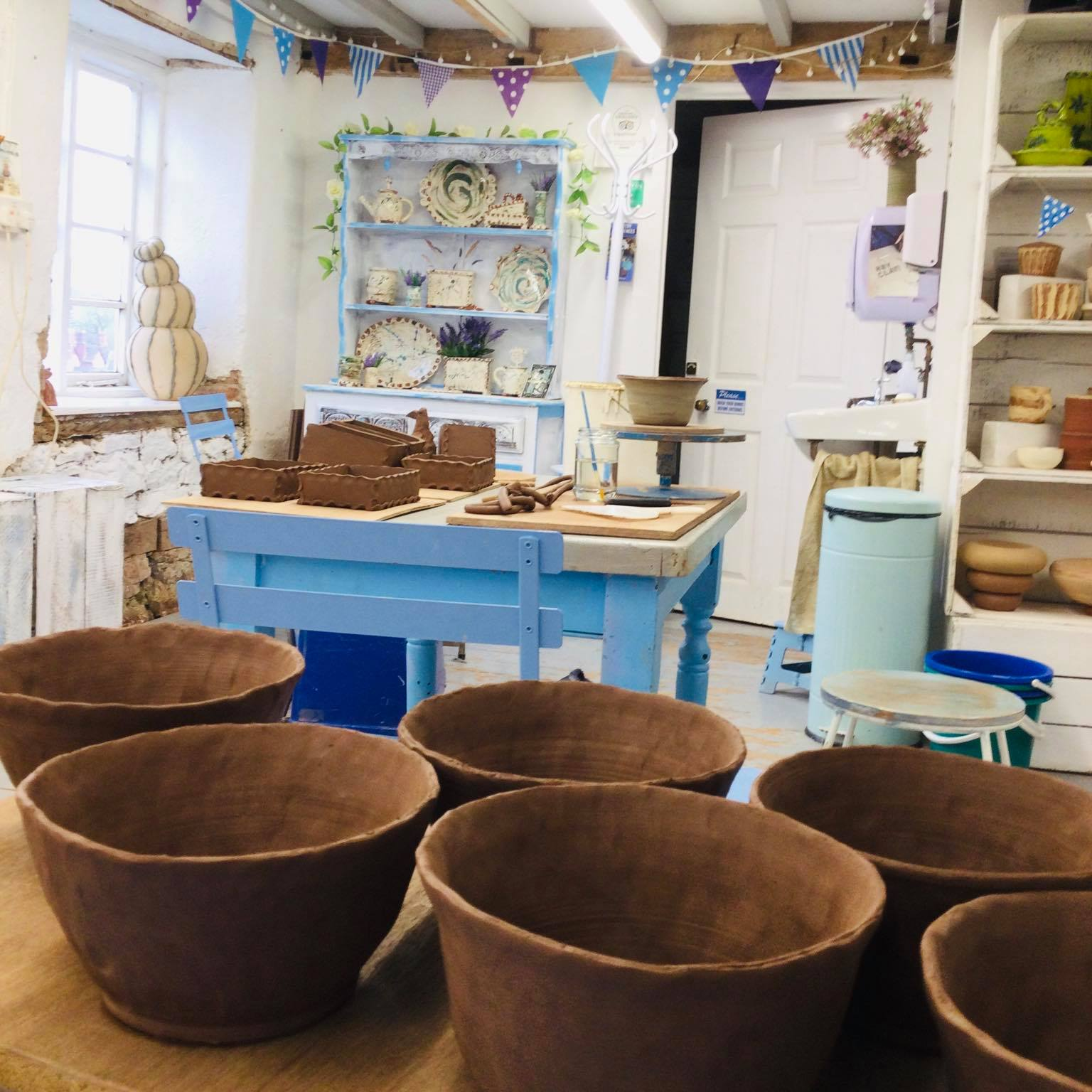 terracotta clay pots waiting to be decorated with slip in the studio of sarah monk ceramics